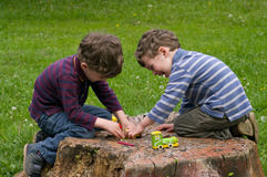 Twins play with one another. Identical twins sit on the stump of the tree and play with interest. They are laughing. They dressed in stripy shirts and trousers Stock Photography