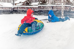 Twins play snowfall time with the inflatable sledge Stock Image