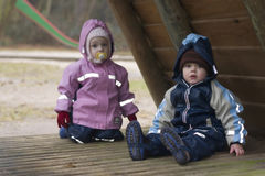 Twins on playground. Three year old twins in winter coats on playground Royalty Free Stock Photography