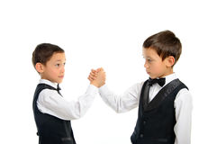 Twins playing arm wrestling isolated. Two brothers twins playing arm wrestling isolated on white background Royalty Free Stock Images