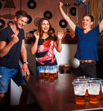 Twins playing beerpong with beautiful brunette in bar Stock Images