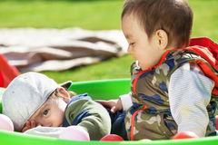 Twins playing. Boy twins playing on the playground (focus on the right boy stock images