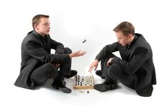 Twins playing chess Stock Images