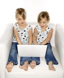 Twins playing on computer. Stock Image