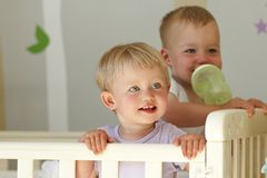 Twins in crib, twin baby boy and girl - together Royalty Free Stock Image