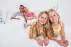 Twins posing in bed in front of their parents Stock Photography