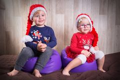 Twins posing in christmas hats Royalty Free Stock Photography