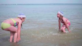 Two funny girls splashing water on the beach. Twins pour water on a hot summer day, laughter and good mood of children. Twins pour water on a hot summer day stock video