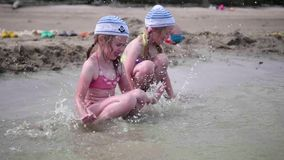Two girls splashing water on the beach. Twins pour water on a hot summer day, laughter and good mood of children. Twins pour water on a hot summer day, laughter stock video