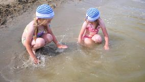 Two girls splashing water on the beach. Twins pour water on a hot summer day, laughter and good mood of children. Twins pour water on a hot summer day, laughter stock footage