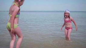 Two little girls play on the sea. Children poured water, create spray. Hot summer day, cheerful mood. Twins pour water on a hot summer day, laughter and good stock footage