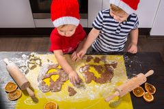 Twins preparing Christmas cookies in the kitchen Stock Image