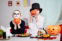 Twins with pumpkins. Photo of twin eerie boys holding Halloween pumpkins by their faces and looking at camera royalty free stock photos