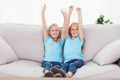Twins raising their arms sitting on a couch Stock Photos