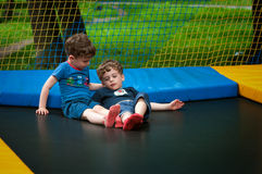 Twins are resting on the trampoline. Identical twins are resting on the trampoline. One of them sits and comforts the other. The boys are tired and calm. They Royalty Free Stock Photos