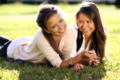 Twins of sister. On the green grass Royalty Free Stock Photos