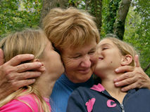 Twins, sister kiss a grandmother. Two blond sisters - twins with closed eyes  kiss the happy -  older person (grandmother) on the cheek and laughing, happy and Royalty Free Stock Photography