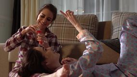 Twins sisters having fun blowing bubbles wearing pretty pajams. Girls have fun. Relationship sisters.