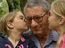 Twins, sisters kiss to grandfather Royalty Free Stock Photo