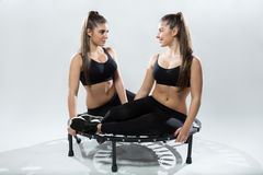 Twins sisters on rebounder Royalty Free Stock Photos