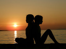 Twins sisters resting in the sunset. The young sisters sitting in the beautiful golden sunset leaning on each other on holiday at Adriatic sea (Croatia-Dalmatia Stock Photography