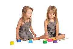 Twins sisters in rompers with paints isolated Royalty Free Stock Photography