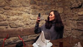 Twins sisters taking pictures of each other in a vintage cafe stock video footage
