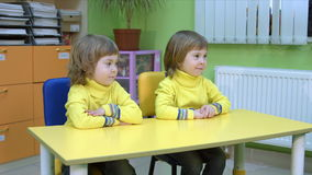 Twins siting at a table stock footage