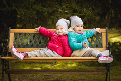 Twins are sitting back to back on the bench royalty free stock image
