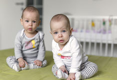 Twins sitting on bed. Beautiful twins sitting on bed. 6 months old stock photo