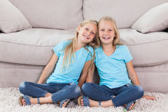 Twins sitting on a carpet Royalty Free Stock Photography