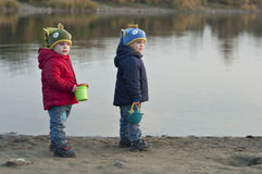 Twins stand near the lake with buckets Royalty Free Stock Images