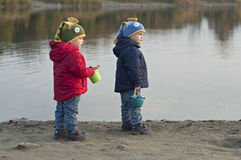 Twins stand near the lake with buckets Royalty Free Stock Photo
