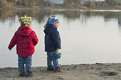 Twins stand near the lake. Twins stand near the water and enjoy the view. Season - autumn. Boys in different jackets and caps Stock Photos