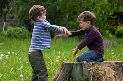 Twins start a fight. Identical twins sit on the stump of the tree and start a fight with hands. They dressed in stripy shirts and trousers different colors. They Stock Photography