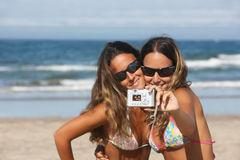 Twins taking a photo. Of themselves on the beach Royalty Free Stock Image