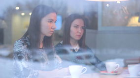 Twins talking with a friend while looking at each other in cafe stock video footage