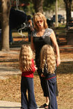Twins in trouble. Grandmother talking to twin children about safety at the park stock photography
