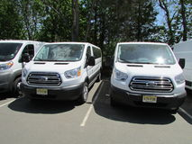 Twins. Two similar Ford minivans. Two similar white passenger minivans on parking lot Stock Photography