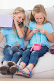 Twins unwrapping birthday gift sitting on a couch Stock Images