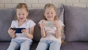 Twins using smatphones on sofa. Two little girls in casual outfits playing games on smartphones while sitting on comfortable couch at home together stock video