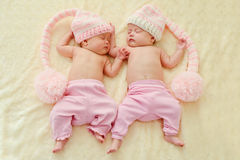 Twins wearing funny hats stock photography