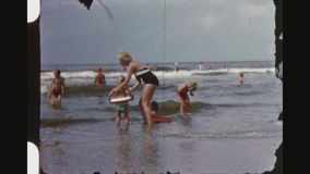 Twins wearing rescue rings playing with the waves. Netherlands, Noordwijk, Summer 1956. Four shot sequence of two little blond girl twins wearing swim rings stock video footage