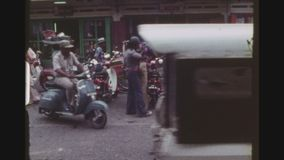 Twins Wearing Same Outfit. INDONESIA, BALI DENPASAR, FEBRUARY 1977. Two Shot Sequence Of Busy Gajah Mada Street Intersection, With Many Motorbikes And Two Female stock footage