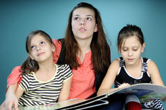 Twins and young educator studying. And reading book Stock Images