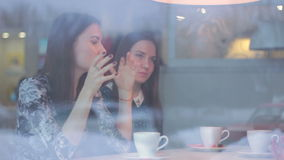 Twinsl young girls talk in a cafe in winter.  stock video footage