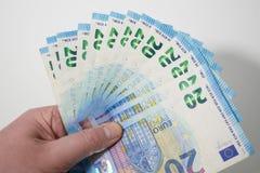 Twintig Euro die bankbiljetten uit in de hand van een Kaukasisch mannetje tegen witte achtergrond worden gewaaid stock foto