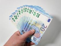 Twintig Euro die bankbiljetten uit in de hand van een Kaukasisch mannetje tegen witte achtergrond worden gewaaid Europees geld royalty-vrije stock afbeelding