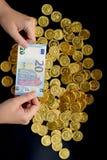 Twintig euro op hand en gouden muntstukken Royalty-vrije Stock Fotografie