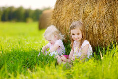 Twio little sisters sitting on a haystack Royalty Free Stock Images